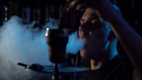 Silhouet van een jonge mens die een waterpijp in de donkere, langzame motie roken Close-up stock footage