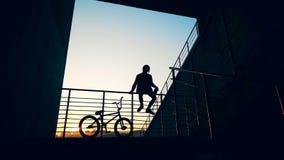 Silhouet van een jonge mensenzitting op traliewerk met een fiets dichtbij hem in de het plaatsen zon stock footage