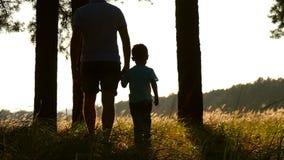 Silhouet van een jonge vader en een zoon die door het hout bij zonsondergang lopen Twee reizigers Close-up Het concept van stock footage