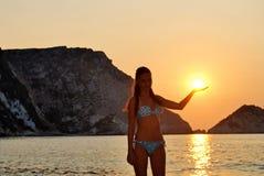 Silhouet van een jonge vrouw die de zon in haar hand houden royalty-vrije stock afbeelding