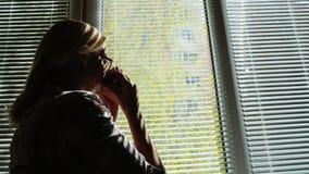 Silhouet van een jonge vrouw door het venster Hij bekijkt de straat door de zonneblinden, drinkt koffie van een kop kijkt stock video