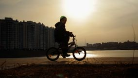 Silhouet van een jongen die een Fiets in het Park berijden stock video