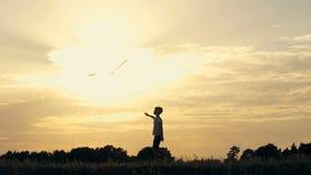 Silhouet van een jongen die met een vlieger op het gebied bij zonsondergang lopen stock footage