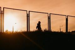 Silhouet van een jongen op een voetbalgebied bij zonsondergang in de zomer Stock Foto