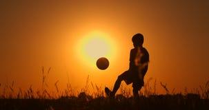Silhouet van een jongens speelvoetbal bij zonsondergang Een jongen jongleert met een bal op het gebied bij zonsondergang stock videobeelden