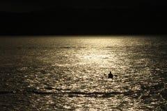 Silhouet van een kayaker bij zonsondergang Royalty-vrije Stock Afbeeldingen