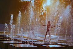 Silhouet van een kind die met een nevel van een fontein op een hete de zomerdag spelen Stock Afbeeldingen