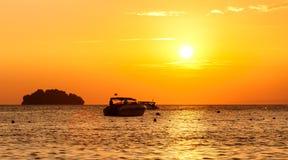 Silhouet van een kleine eiland en een kleine boot bij zonsondergang Stock Afbeeldingen