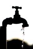 Silhouet van een kraan druipend water stock fotografie