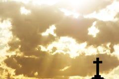 Silhouet van een kruis over gloeiende wolken stock foto's