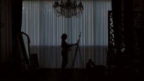 Silhouet van een kunstenaar die op canvas in een tekeningsstudio trekt stock videobeelden