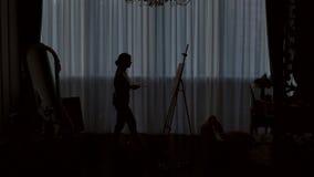 Silhouet van een kunstenaar die op canvas in een tekeningsstudio trekt stock video