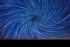 Silhouet van een kussend paar onder sterslepen stock afbeeldingen