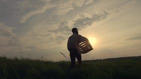 Silhouet van een landbouwer met een doos stock footage