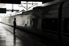 Silhouet van een man of een vrouw op het station in dark Concept eenzaamheid Een passagier die op de trein wachten royalty-vrije stock afbeeldingen