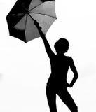 Silhouet van een meisje die een paraplu houden Stock Afbeelding