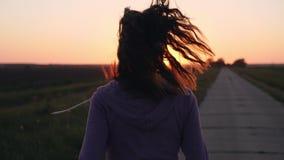 Silhouet van een meisje die langs de weg lopen stock footage