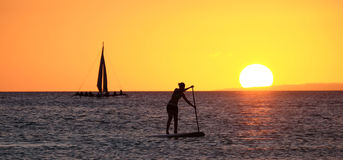Silhouet van een meisje die op de sup surfplank drijven Royalty-vrije Stock Foto's