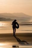Silhouet van een meisje die op het strand lopen Stock Foto's