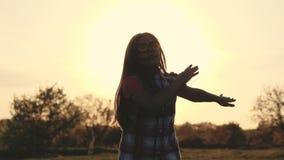 Silhouet van een meisje die op zonsondergang dansen stock videobeelden