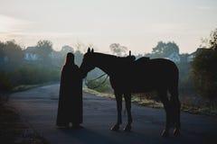 Silhouet van een meisje in een regenjas die een paard op donkere achtergrond met blauwe mist kussen Royalty-vrije Stock Fotografie