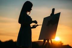 Silhouet van een meisje Het blondemeisje schildert het schilderen op het canvas met behulp van verven Royalty-vrije Stock Foto