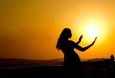 silhouet van een meisje met dunne taille en handen uitgestrekt aan de zon bij zonsondergang Stock Fotografie