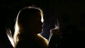 Silhouet van een meisje met een kop van hete thee in dark stock video