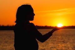 Silhouet van een meisje op de achtergrond van de avondzon, rode zonsondergang royalty-vrije stock afbeeldingen