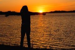 Silhouet van een meisje op de achtergrond van de avondzon, rode zonsondergang royalty-vrije stock foto