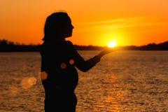 Silhouet van een meisje op de achtergrond van de avondzon, rode zonsondergang royalty-vrije stock fotografie