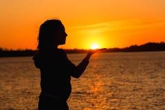 Silhouet van een meisje op de achtergrond van de avondzon, rode zonsondergang stock foto's