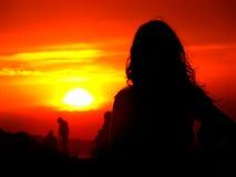 Silhouet van een meisje op een achtergrond van een zonsondergang Royalty-vrije Stock Afbeelding