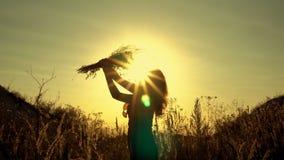 Silhouet van een meisje tegen de heldere stralen van de het plaatsen zon met een boeket van wildflowers in zijn handen Zij snuift stock video
