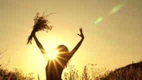 Silhouet van een meisje tegen de heldere stralen van de zon, zij die een boeket van wildflowers golven bij de zonsondergang van d stock footage