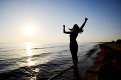 Silhouet van een meisje tegen de zonsondergang door het overzees Royalty-vrije Stock Foto