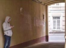 Silhouet van een mens in de kap met de telefoon die zich in de binnenplaatsboog bevinden stock fotografie