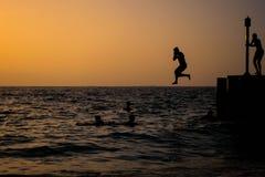 Silhouet van een mens die aan het water springen Stock Foto's