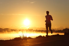 Silhouet van een mens die bij zonsopgang lopen