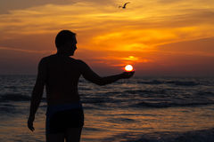 Silhouet van een Mens die de Zon houden stock afbeelding