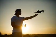 Silhouet van een mens die hommel met één hand en ver controlemechanisme in een andere hand op zonsondergang vangen Veilige quadco stock foto's