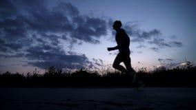 Silhouet van een mens die op de weg bij zonsondergang lopen stock videobeelden