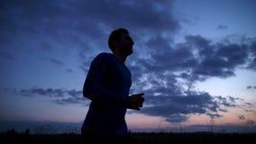 Silhouet van een mens die op de weg bij zonsondergang lopen