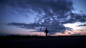Silhouet van een mens die op de weg bij zonsondergang lopen stock footage