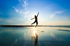 Silhouet van een mens die over zon springen royalty-vrije stock foto