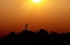 Silhouet van een mens die zich bovenop een heuvel bevinden Royalty-vrije Stock Afbeeldingen