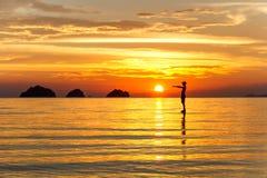 Silhouet van een mens die zich in het overzees bij de achtergrond van zonsondergangeilanden op een tropisch eiland bevinden Royalty-vrije Stock Afbeeldingen