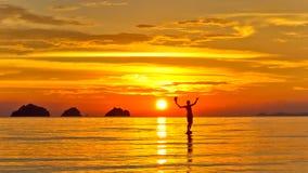 Silhouet van een mens die zich in het overzees bij de achtergrond van zonsondergangeilanden op een tropisch eiland bevinden Stock Afbeeldingen