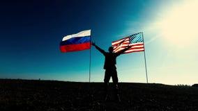 Silhouet van een mens met Amerikaanse vlag en Russische vlag die zijn wapens golven stock footage