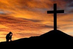 Silhouet van een mens met een kruis Stock Fotografie